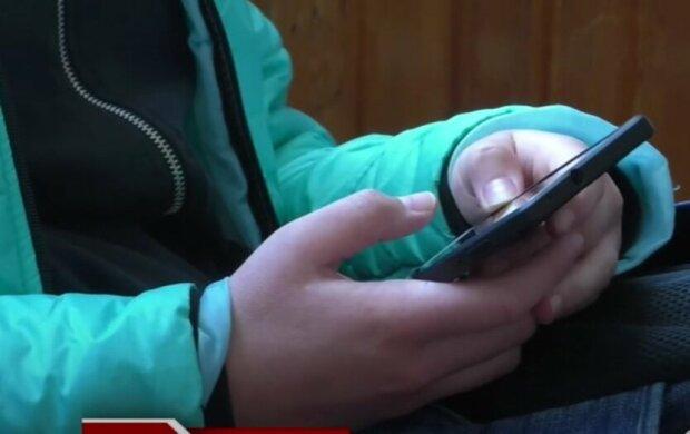 дитина тримає телефон, ілюстративне фото з вільних джерел