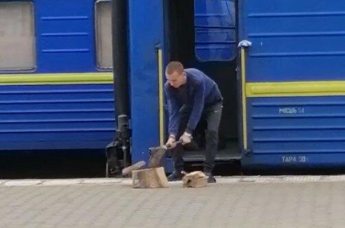 """Проводник """"Укрзализныци"""" готовит дрова на перроне для обогрева в поезде: не нарубишь – не поедешь"""