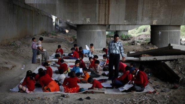 Два стульчика и бесплатные сидячие места на земле: импровизированная школа под мостом. Дети готовы учиться любой ценой