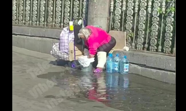 """В Киеве женщина устроила """"большую стирку"""" прямо на улице: сливала прямо под ноги пешеходам"""