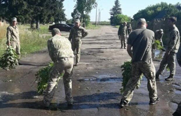 Зеленский едет: военных заставили бутылками и лиственными вениками осушать лужи